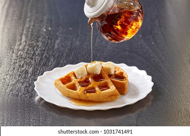 Waffles and butter are placed in a white dish topped with honey syrub in a jar