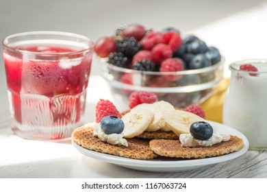 Waffles with cheese, yogurt and raspberries. A delicious wholesome breakfast on a light background. Very soft selective focus.