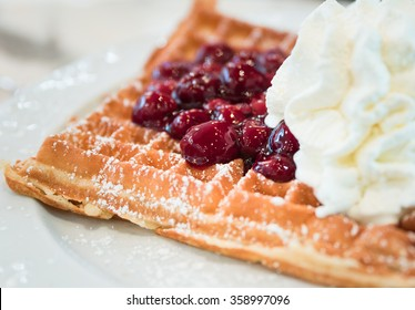 Waffles with cherries and whipped cream
