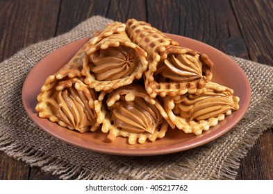 Waffles cones with boiled condensed milk in plate on dark wooden table