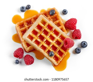 waffles decorated with honey and berries isolated on white background, top view