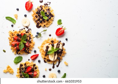 Waffles with fresh berries - strawberry, blueberry, bananas and chocolate topping. Sweet dessert on white background. Top view space for text.
