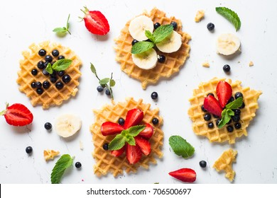 Waffles with fresh berries - strawberry, blueberry, bananas and chocolate topping. Sweet dessert on white background. Top view.