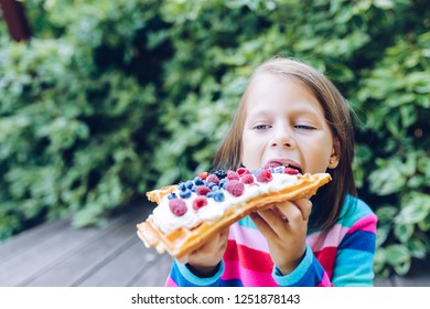 waffles - girl eating a waffle with whipped cream, raspberries and blueberries outdoors  in the garden smiling
