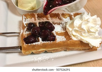 Waffles with hot cherries and cream