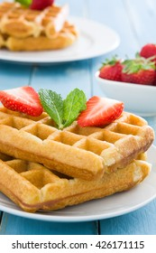 Waffles with ice cream on blue wood