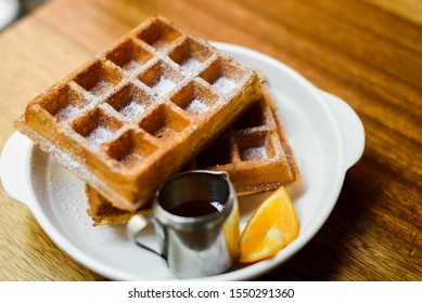 The waffles are icing powder and served with honey and lemon. Served on a white plate, select focus