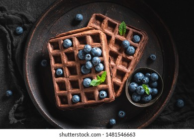 Waffles made of cocoa with berry fruits on dark table
