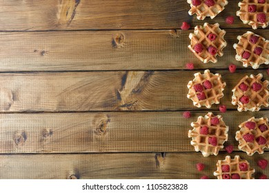 Waffles with raspberries on a wooden background