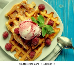 Waffles with raspberry ice cream and fresh raspberries, decorated with mint over blue wooden background, close up