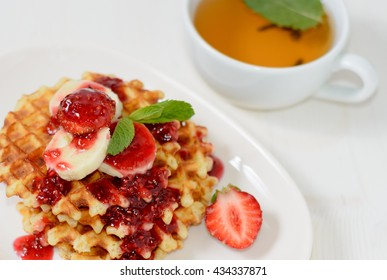Waffles with strawberries bananas and mint, cup of tee for healthy dessert breakfast
