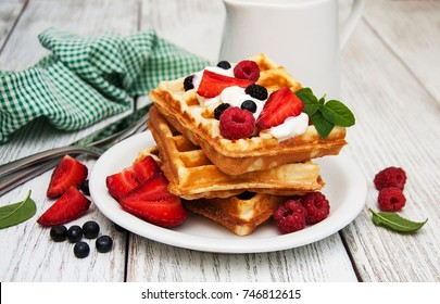 waffles with strawberries,  blueberry and milk on a old wooden table