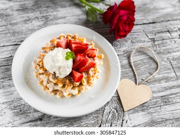 waffles with strawberries and vanilla ice cream, red rose and paper heart on a light wooden background