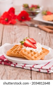 Waffles with strawberries and whipped cream.