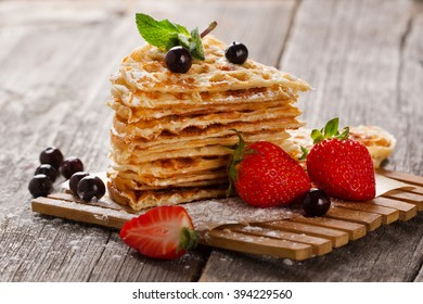 Waffles with strawberry on wood table