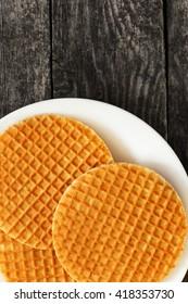 Waffles stroopwafel on a plate on dark wood. Sweet food for breakfast