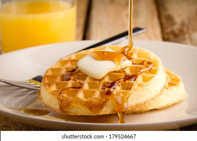 Waffles - This s a photo of a couple waffles being soaked in syrup. Shot on a wooden table with a shallow depth of field.