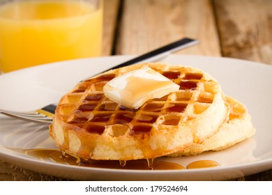 Waffles - This s a photo of a couple waffles soaked in syrup. Shot on a wooden table with a shallow depth of field.