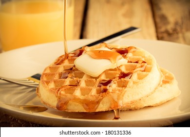 Waffles - This s a photo of a couple waffles being soaked in syrup. Shot in a warm retro color tone with a shallow depth of field.