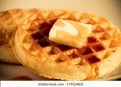 Waffles - This is a shot of a couple waffles with a slice of butter sitting on a plate getting covered with syrup. Shot with a shallow depth of field in a warm retro color tone.