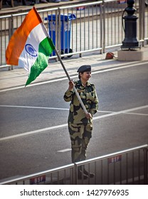 Wagah border, Punjab,  India - April 14th, 2019 : A lady officer of Indian Border Security Force, waving Indian National Flag during evening military drill jointly done by Indian & Pakistani forces.