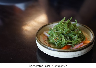 Wagame seaweed salad with crab stick and sesame in white stone plate, the Japanese appetizer small dish, put on the brown wooden table with dim light
