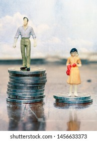 wage inequality concept  with male and female figurines on coins ,maceo image