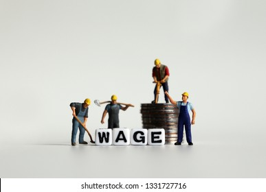 'WAGE' word in white cube. Miniature people and pile of coins.