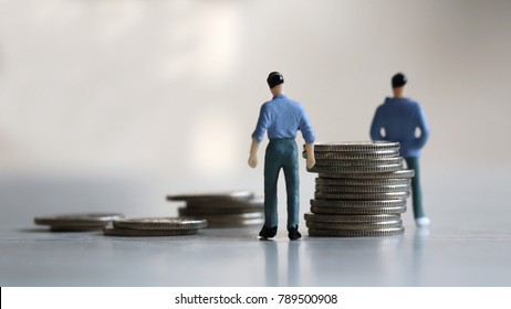 Wage and work. Appearance from behind of two miniature man standing between a pile of coin.