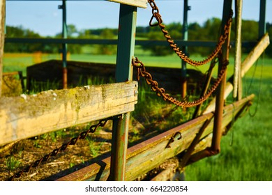 Wagon with a rusty chain and a green field in the background