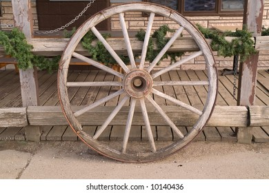 Wagon wheel leaning against a fence with a touch of green looks appealing, feels inviting