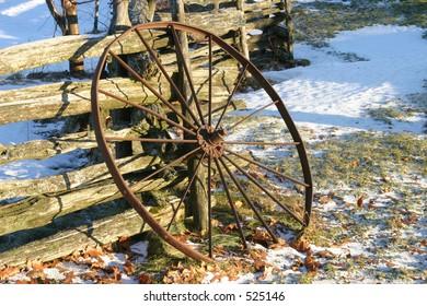 Wagon Wheel Leaning on Wood Rail Fence
