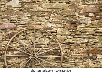 wagon wheel and stone wall