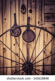 Wagon wheel with western themed objects and worn weathered wood.