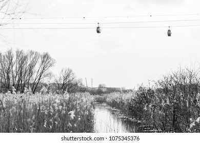 Wagons of a cable car over the natural landscape. Black and white.