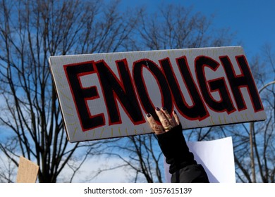 "WAHINGTON, DC/USA- March 24, 2018: A woman holds an ""ENOUGH""  protest sign at student The March For Our Lives demonstration in Washington, DC on March 24, 2018."