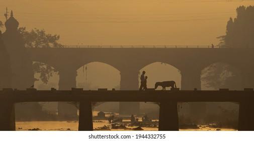 WAI, MAHARASHTRA, INDIA-FEB 05,2009 : Silhouette image of early Morning activities in golden light during Sun rise on bank of Krishna river, Menavali Ghat, WAI, MAHARASHTRA INDIA.