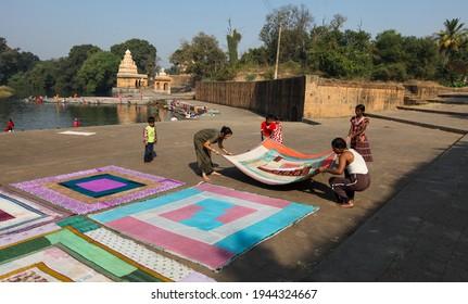 WAI, MAHARASHTRA, INDIA-FEB 05,2009 : Village Women washing clothes and colourful handmade mattress drying on bank of Krishna river, Menavali Ghat, WAI, MAHARASHTRA INDIA.