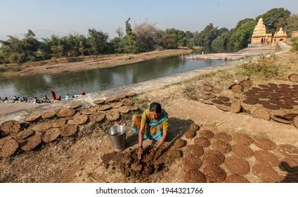 WAI, MAHARASHTRA, INDIA-FEB 05,2009 : Women making cow dung cakes on a bank of Krishna river, Menavali Ghat, WAI, MAHARASHTRA INDIA.
