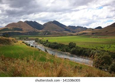 Waiau River gently meandering through green fields, under the overcast skys, after its voyage through the mountains.