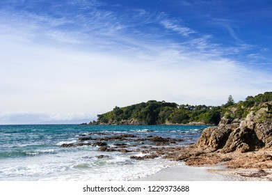 Waiheke Island, New Zealand. Picturesque bay surrounded by lush greenery with blue sky background