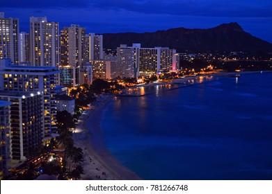 Waikiki Beach, HI, USA August 2, 2014 The lights of the resorts on Waikiki Beach, Hawaii, glitter under the looming Diamond Head Mountain