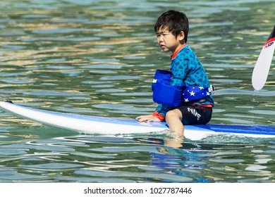 WAIKIKI BEACH, HONOLULU, HAWAII - FEBRUARY 10, 2018: A young man catches a ride from a stand up paddle boarder paddling out to sea from Waikiki Beach.