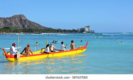 WAIKIKI BEACH, HONOLULU, HAWAII - March 27: People in an outrigger canoe paddle out to sea under the supervision of an experienced beach boy on March 27, 2015 on Waikiki Beach.