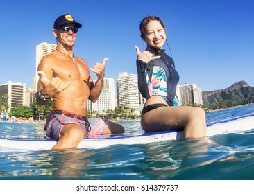 WAIKIKI BEACH, HONOLULU, HAWAII - MARCH 18, 2017: An unidentified young man and woman sitting on a surfboard give the Hawaiian Shaka while waiting for the next big wave. On the right is Diamond Head.