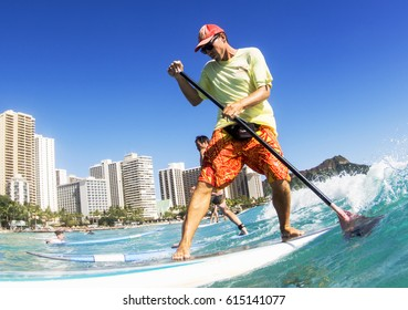 WAIKIKI BEACH, HONOLULU, HAWAII - MARCH 18, 2017: Close-up of surfers catching a wave off Waikiki Beach. In the background are luxury hotels and Diamond Head.