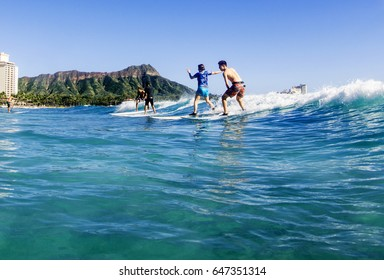 WAIKIKI BEACH, HONOLULU, HAWAII - MARCH 18, 2017: Surfers catch a wave at Waikiki Beach on a sunny afternoon. In the background are luxury hotels and Diamond Head.