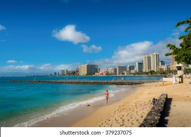 Waikiki Beach, Honolulu, Hawaii, USA - December 11, 2015: Waikiki Beach in the afternoon sun. Hotels dot the skyline in the distance.