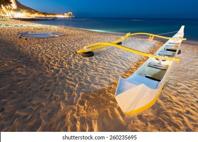 Waikiki beach at night with a yellow outrigger canoe