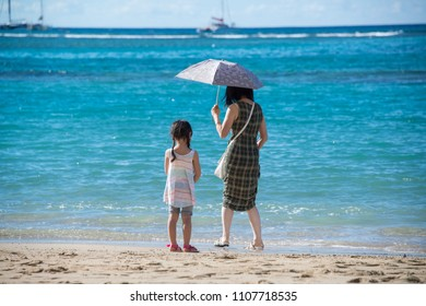 Waikiki Beach, Oahu, HI, USA 1-30-2018: Mother and daughter little girl playing in the gentle blue waves at the sandy beach